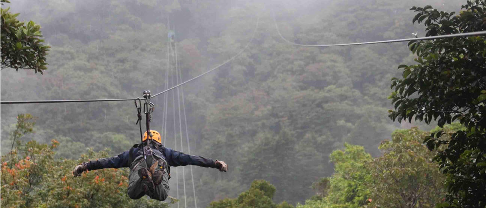 Monteverde Costa Rica zipline adventure guest zipping superman style soaring through cloud forest with arms spread apart