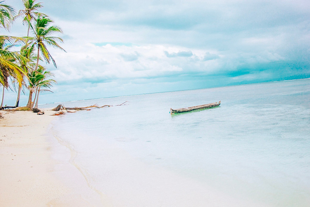 remote san blas panama island with local kuna canoe in clear ocean water