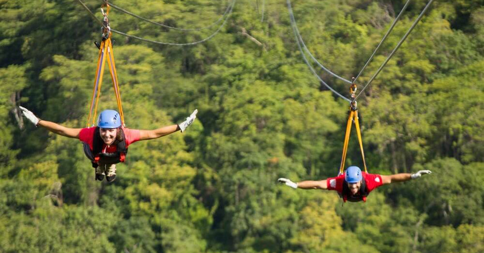 ziplining in Costa Rica man and woman zipping superman styke with outstretched arms across rainforest valley