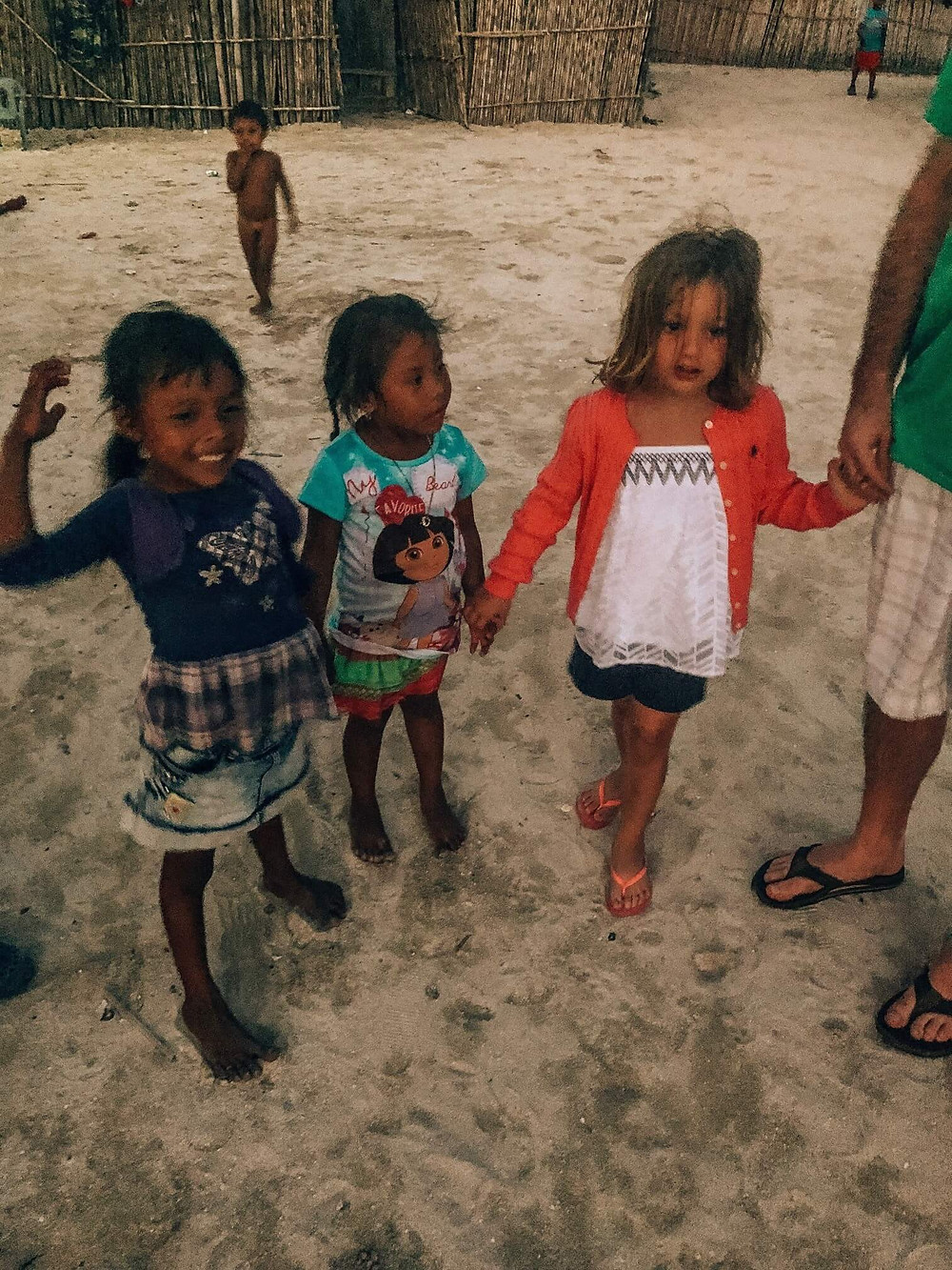 local kuna kids holding hands and playing with tourist kids in san blas panama