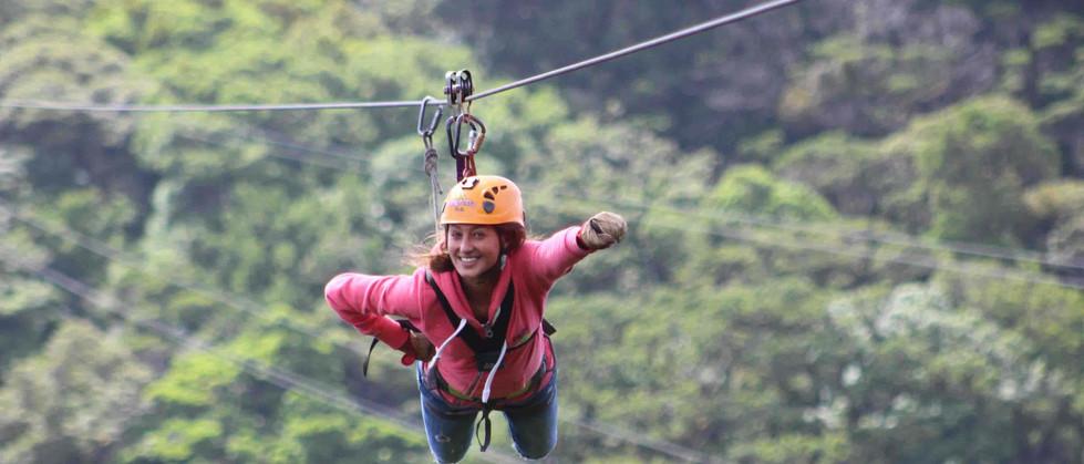 Monteverde Costa Rica zipline adventure woman guest zipping superman style accross valley.