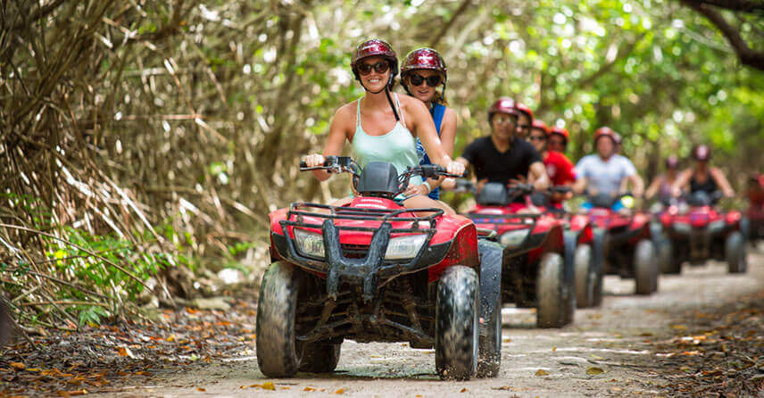 Costa Rica ATV adventure group driving along trail through jungle forest