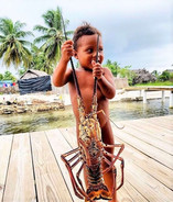 Kuna kid holding up lobster