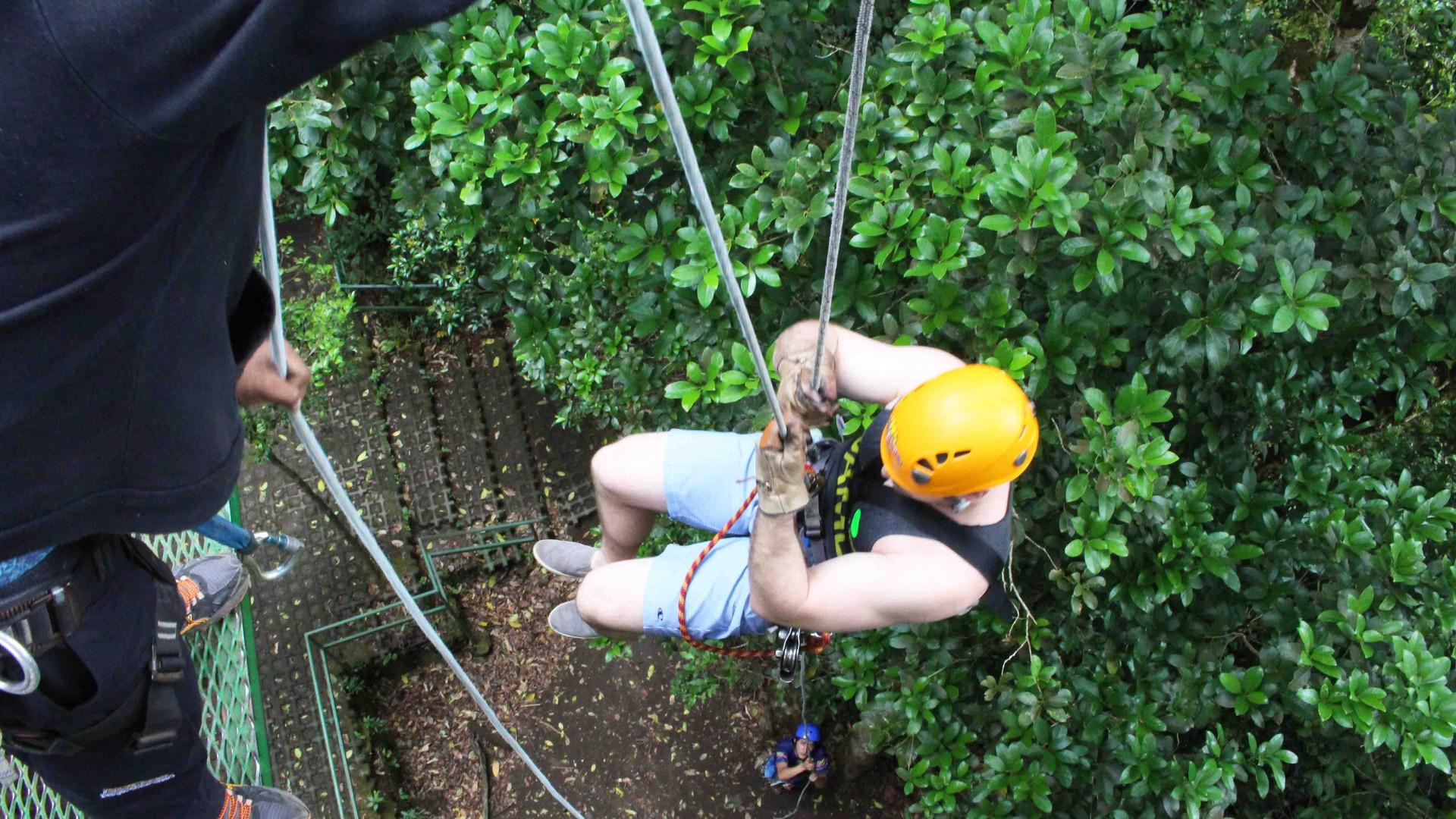 Monteverde Costa Rica zipline adventure guest hanging and rappelling off canopy