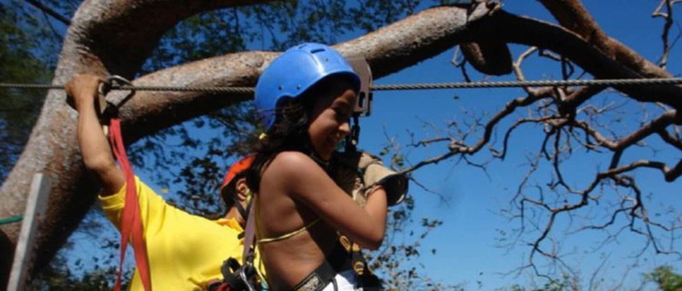 Child hanging on zipline with harness and cable in Tamarindo Guanacaste Costa Rica