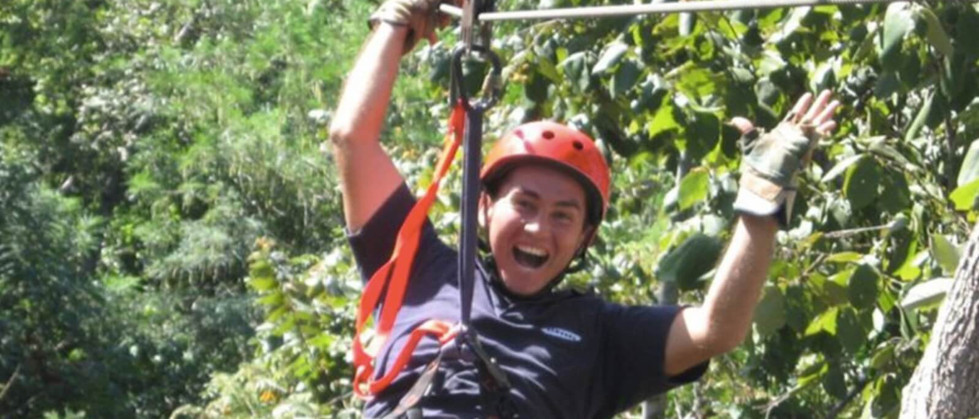 laughing man hanging on zipline with harness and cable in Tamarindo Guanacaste Costa Rica