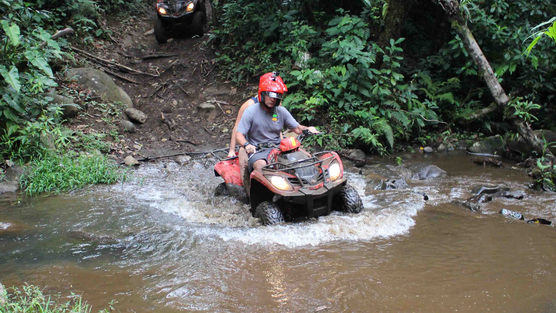 Monteverde Costa Rica ATV adventure tour two guests riding 4x4 with lights on crossing traversing river smiling