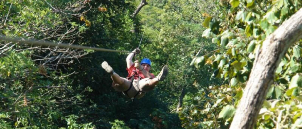 man hanging gliding soaring on zipline with harness and cable in Tamarindo Guanacaste Costa Rica