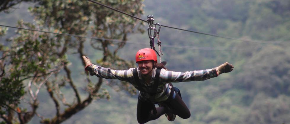 Monteverde Costa Rica zipline adventure guest woman in red helmet zipping superman style with arms spread wide