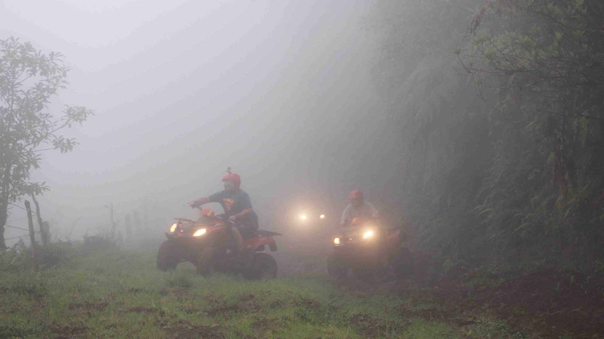 Costa Rica Monteverde Costa Rica ATV adventure tour group riding through dense fog cloud with lights on