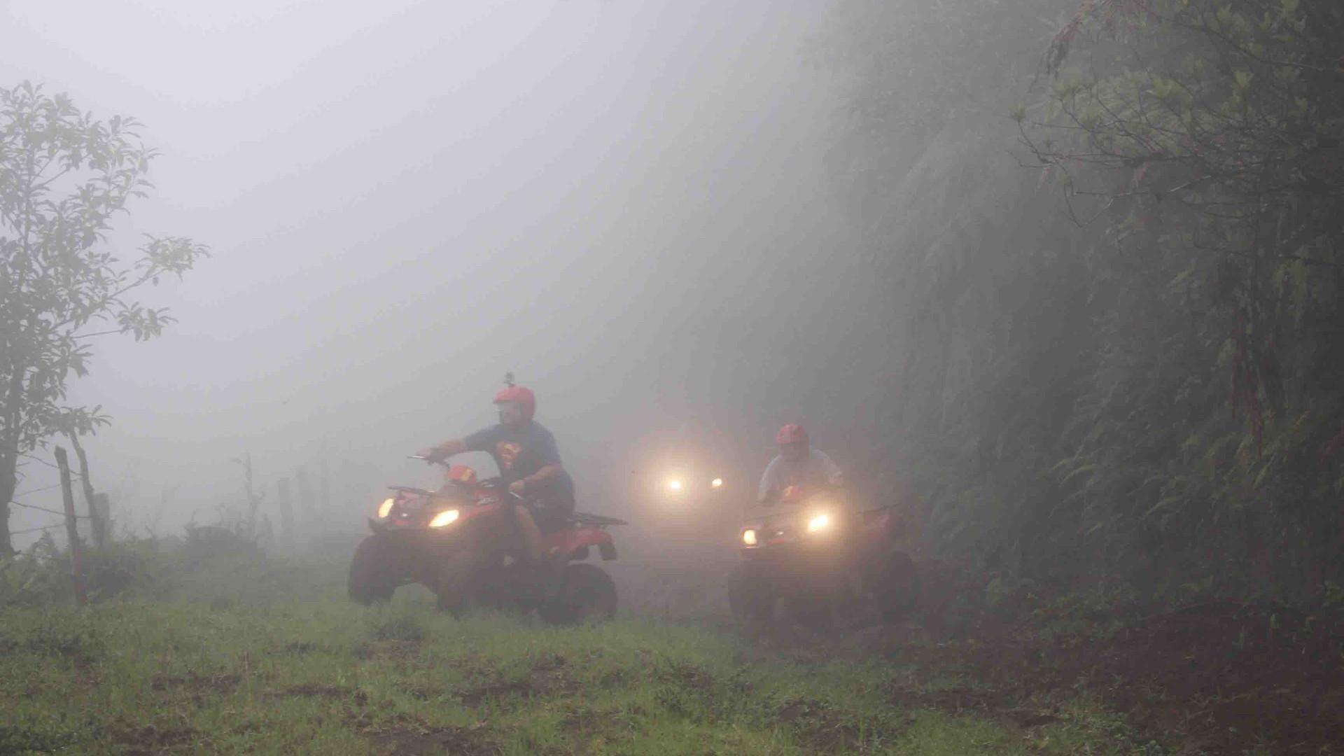 Costa Rica Monteverde Costa Rica ATV adventure tour group riding through dense fog cloud with lights on