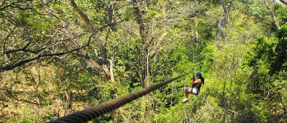 Woman hanging on zipline with harness and cable in Tamarindo Guanacaste Costa Rica