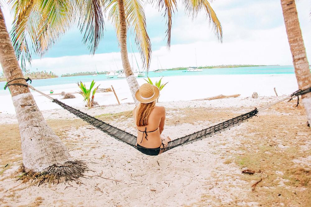 woman sitting on hammock on a san blas island enjoying the view of sailboats