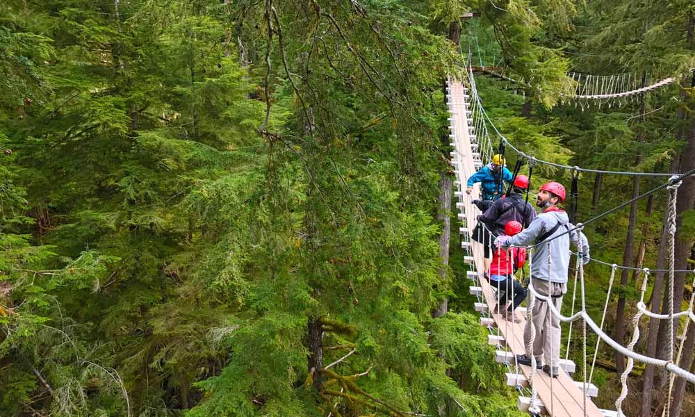 Costa Rican ziplining guests walking across hanging bridge in canopy zipline rainforest valley