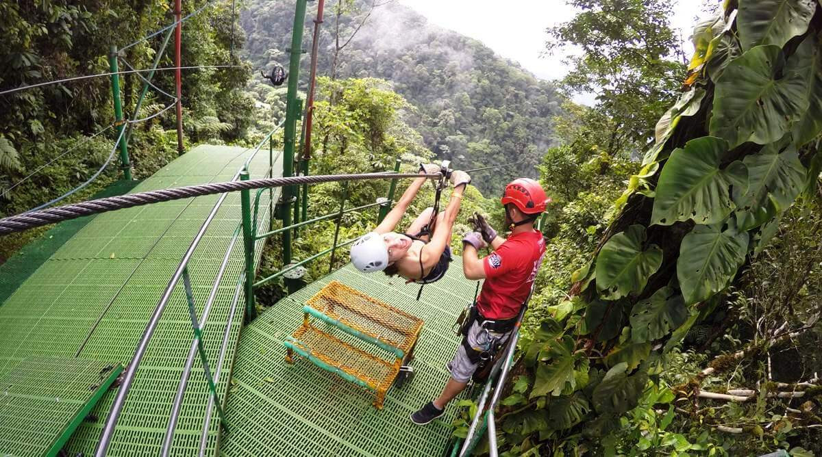 Costa Rica zipline guest with guide getting ready to zip accross rainforest valley