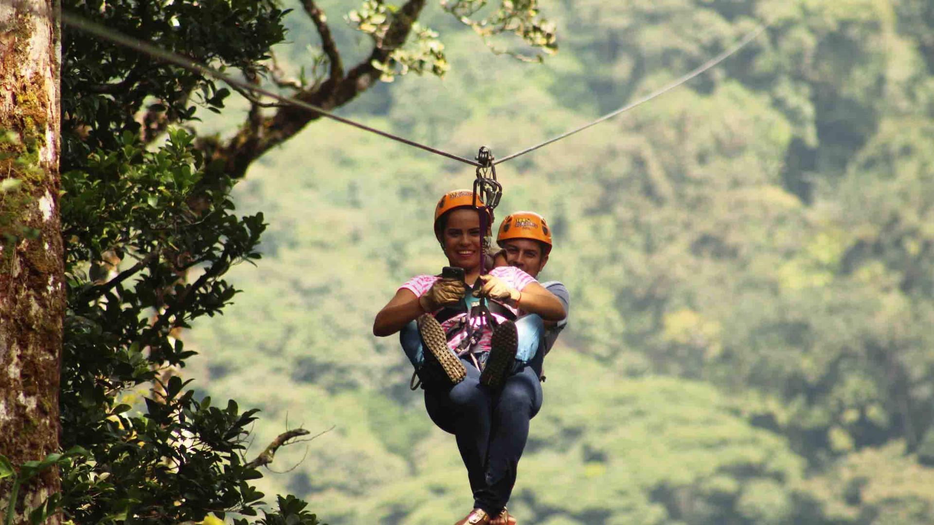 Monteverde Costa Rica zipline adventure guests zipping tandem through lush nature.