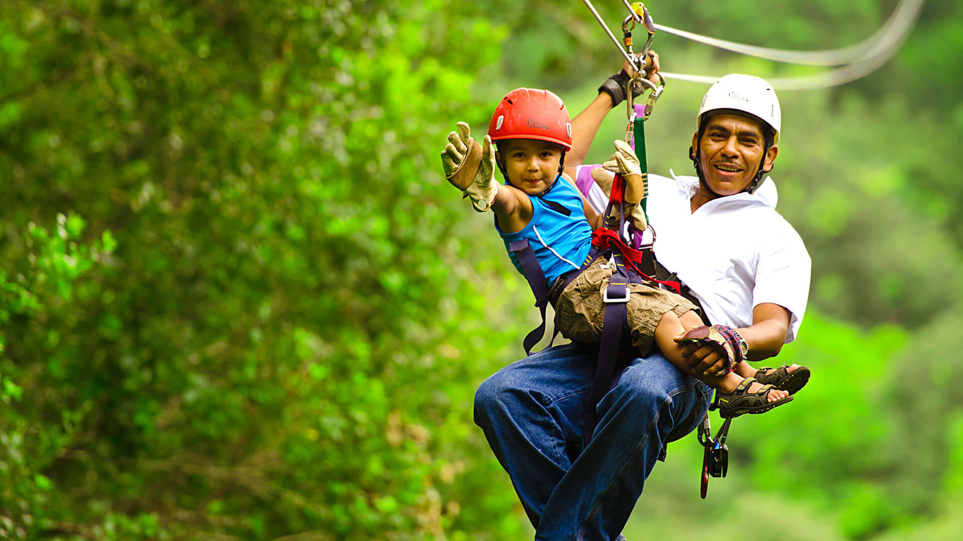 Costa Rica ziplining family adventure Dad and waving son on tandem zipline