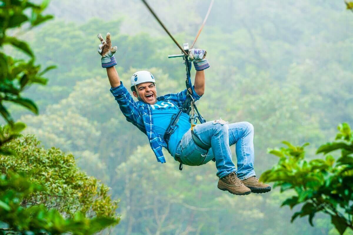 ziplining in Costa Rica smiling man waving and zipping on cable