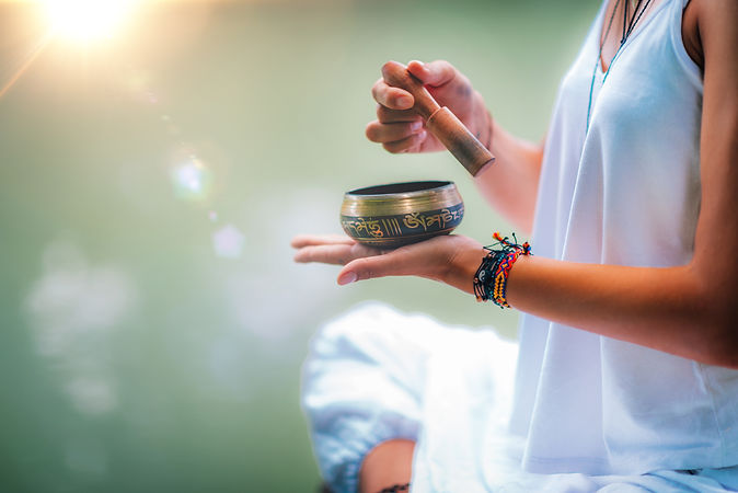 Close up image of woman's hands holding Tibetan bowl by the Water.jpg
