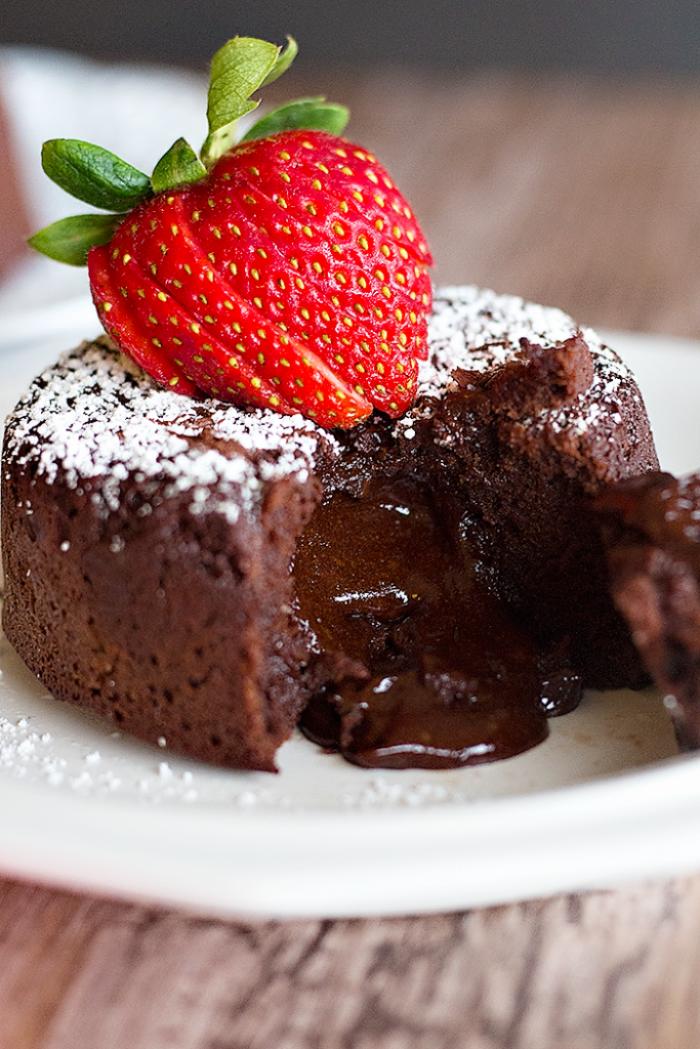 Volcán de chocolate derrampandose sobre un plato blanco con frutilla roja encima