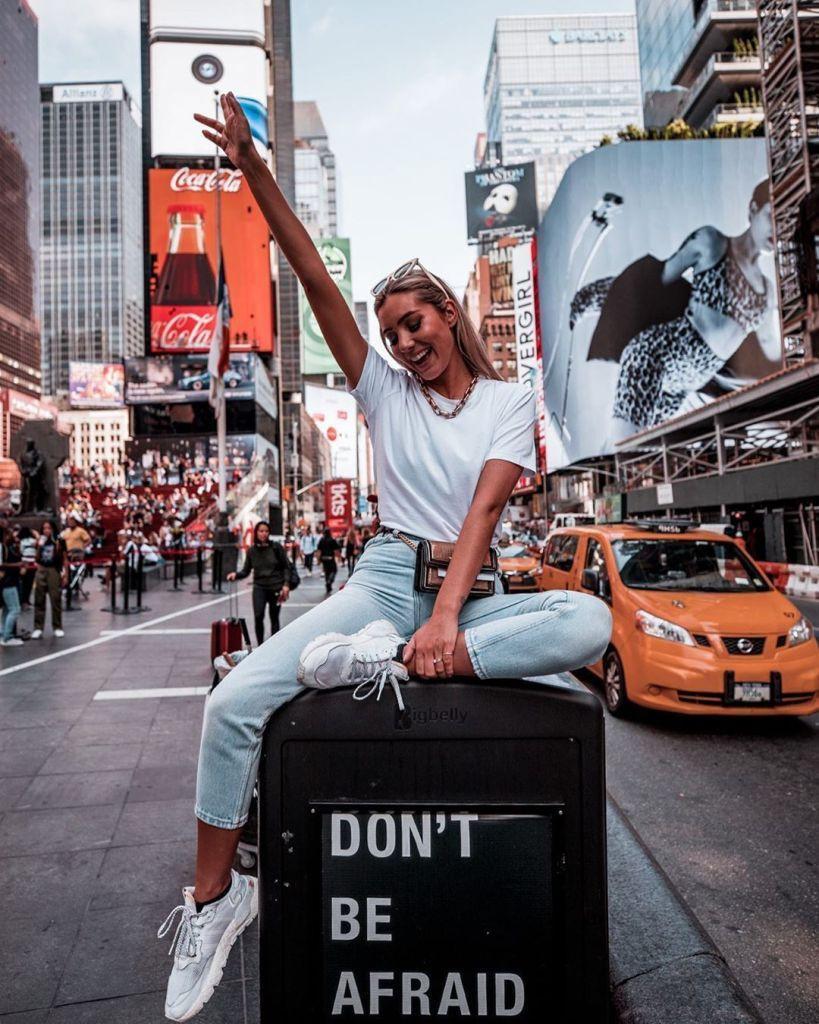 """Mujer rubia en Nueva York. Viste jeans celeste claro, remera y zapatillas blancas. Está sentada sobre un cartel que dice """"don´t be afraid"""""""