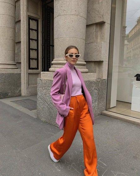 Mujer caminando vestida con chaqueta lila y pantalones anaranjados con zapatillas y anteojos blancos.
