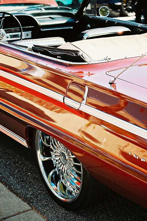Portrait shot of a red chevrolet impala focusing on the rear drivers side rim