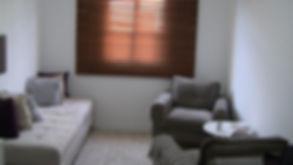 Sala de atendimento psicológico. Com os seguintes méveis: duas poltronas de frente uma com a outra, um divâ ao lado, um tabete no chão, uma cortina de madeira e uma mesa de centro.