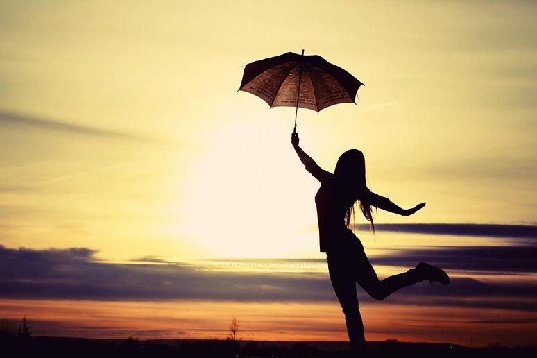 por do sol, uma mulher segurando guarda chuva e dançando.