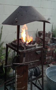 A forge made from a brake drum and scrap steel, with a salvaged squirrel-cage fan for a blower.