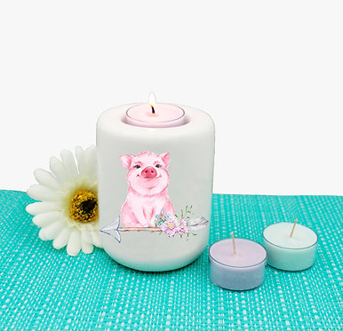 Ceramic tealight candle holder with image of a cute pig sitting on arrow with flowers front view