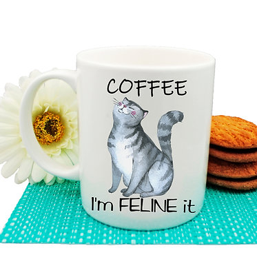 """Ceramic coffee mug cat and quote """"Coffee i'm feline it"""" image front view"""
