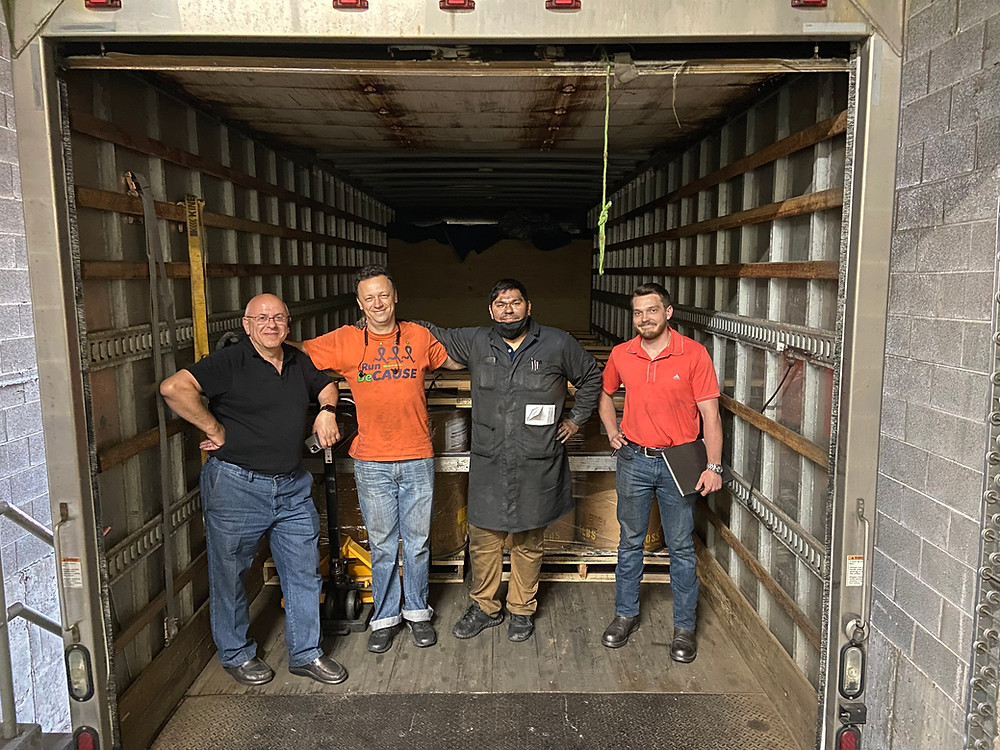 AETC engineers next to their first commercial truckload shipment of advanced battery-ready graphite.