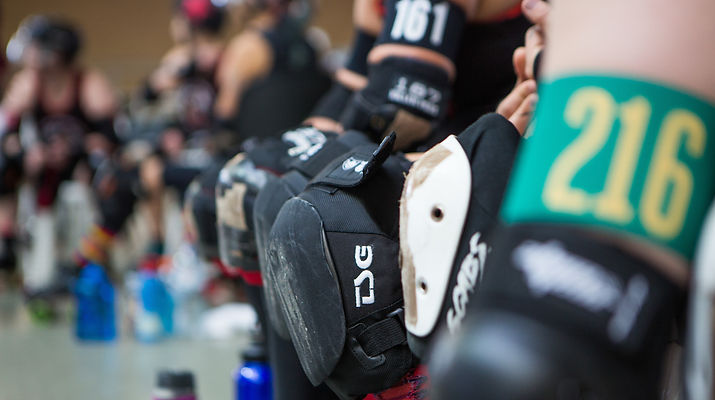 Close up of kneepads and armbands of people sitting on the bench.