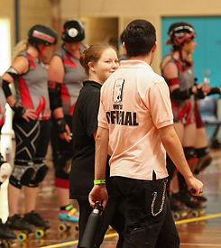 2 officials, one wearing a WFTDA official shirt, talk to each other. Blurred derby skaters in the background.