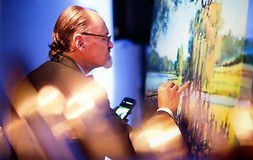 Dan Nelson painting at a reception