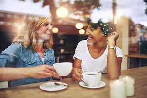 two-multi-ethnic-friends-enjoying-coffee
