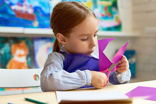 cute-girl-cutting-out-paper-heart-in-cra