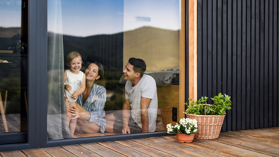 Young family with small daughter indoors, weekend away in container house in countryside..