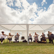 Master fiddle players playing for students at the GAA grounds.