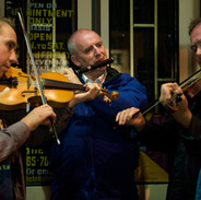 Oisín Mac Diarmada, Marcas Ó Murchú and Antóin Mac Gabhann playing in a session on Miltown Malbay's main street 2009.