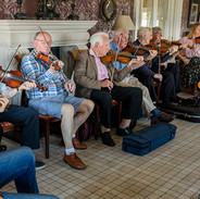 Master fiddle players playing for students.