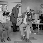 Joe Ryan and Bobby Casey playing for a fiddle class with Breandán Breathnach standing in the centre background, 1985.