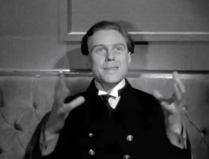 Marius Goring as Lieutenant Felix Schuster in The Spy in Black 1939: he has just come back from 16 days at sea in a U-Boat, eating only tinned sardines, and is describing to the waiter how big he wants his pudding ('As big as a depth charge')