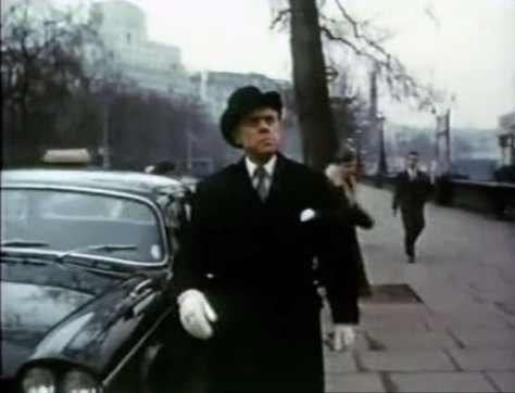 Shevik (Marius Goring) watches his henchmen as they attempt to take Donovan (Gene Barry) captive. Victoria Embankment, London WC2.