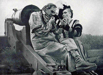 Marius Goring, making up as Osric, is helped by Barbara Dillon, lady to the Queen in 'Hamlet' at Elsinore July 1939