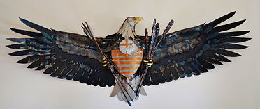 metal sculpture of bald eagle holding arrows and wheat sheaves with shield of American flag on chest.