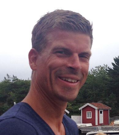 Seilmaker Michael smiler mens han står ved en rød hytte
