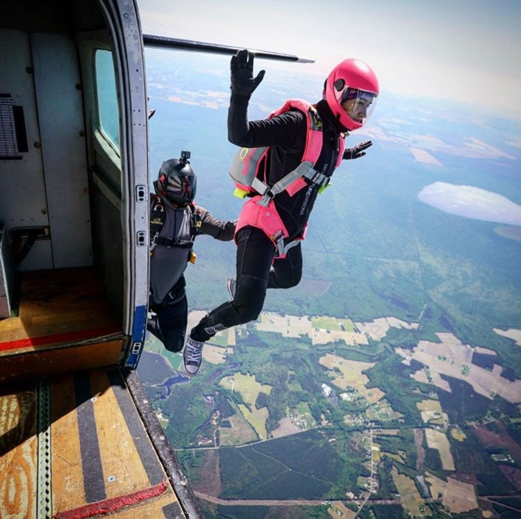 Woman skydiver exits plane during coach course