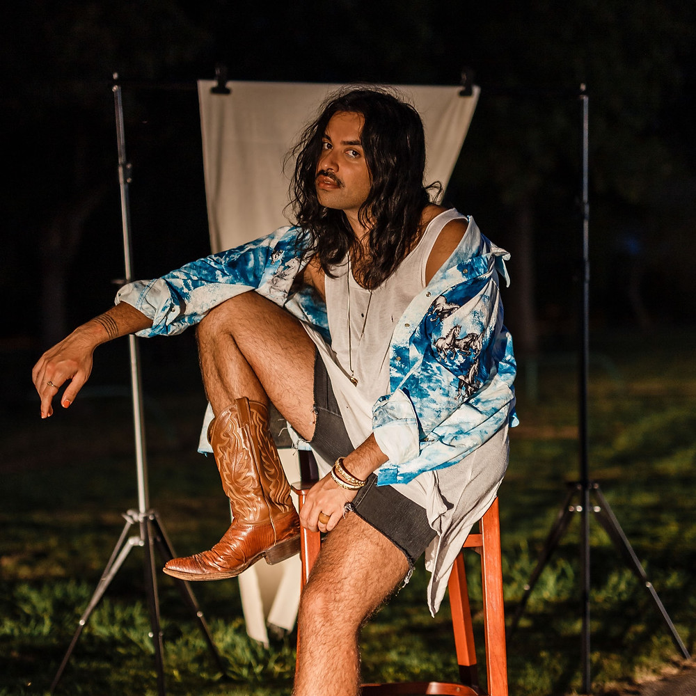Uliya sits on a stool with one leg up and one leg down. They have on black denim shorts, brown cowboy boots, a white tanktop, and a splotchy blue oversized shirt that's open. Their hair is past their shoulders. It's nighttime and their being lit by a headlight.